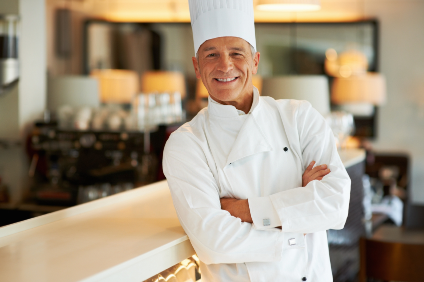 Portrait of smiling cook standing with hands folded in restaurant